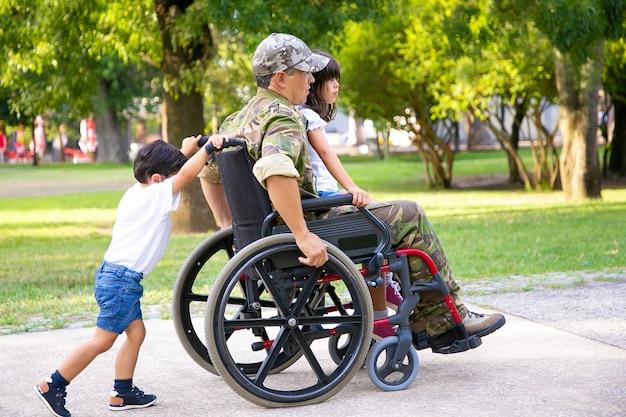 Behinderter pensionierter militärmann, der mit kindern im park geht. mädchen sitzt auf dem schoß des vaters, junge, der rollstuhl schiebt. kriegsveteran oder behindertenkonzept