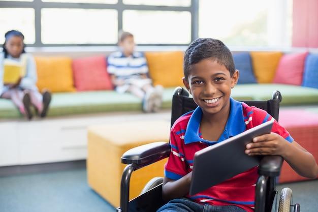 Behinderter schüler auf rollstuhl unter verwendung der digitalen tablette in der bibliothek