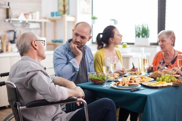 Behinderter senior im rollstuhl, der beim familienbrunch in der küche ein gespräch mit seinem sohn führt. ältere eltern zusammen mit reifen kindern.