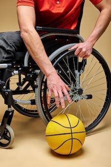 Behinderter sportler, der basketballball vom boden nimmt und sportspiel spielt. isolierter beiger hintergrund
