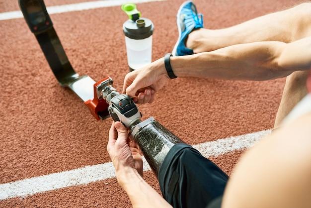 Behinderter sportler, der künstliches glied repariert