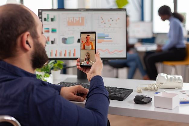 Behinderter ungültiger manager, der per videoanruf mit freunden spricht, die während der arbeitszeit ein smartphone halten