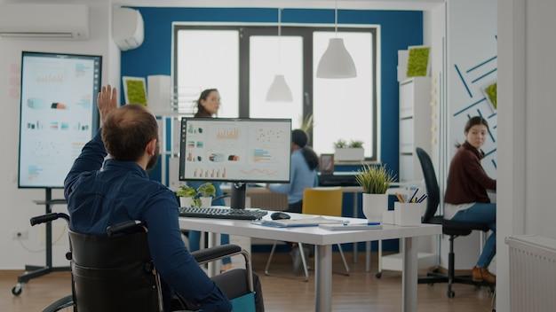 Behinderter unternehmer kommt in start-up-büro kollegen begrüßen