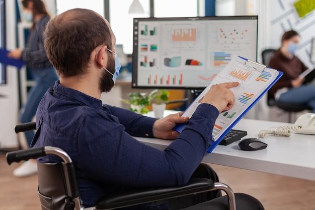Behinderter unternehmer mit gesichtsschutzmaske, der in einem neuen normalen finanzunternehmen arbeitet, das projektdokumente überprüft