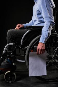 Behinderter verärgerter mann sitzt mit papier auf der arbeitssuche, unglücklich und hoffnungslos. kein soziales leben und unterstützung. abgeschnittener mann, der auf rollstuhl sitzt