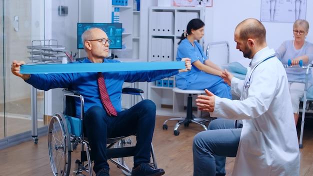 Behinderter verletzter mann trainiert mit gummiband unter strenger ärztlicher aufsicht in einer modernen privaten erholungseinrichtung. ungültiges physiotherapieprogramm, rehabilitation nach gesundheitsschäden