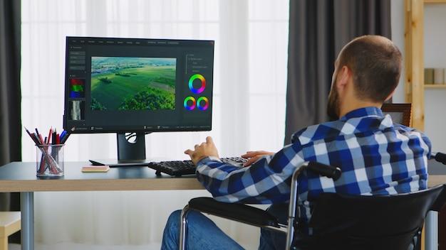 Behinderter videofilmer im rollstuhl, der von zu hause aus arbeitet.