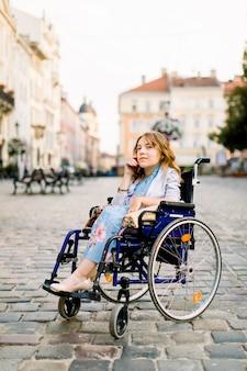 Behindertes junges mädchen im rollstuhl, das auf handy spricht
