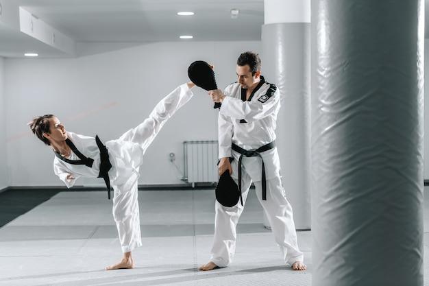 Behindertes mädchen, das taekwondo mit ihrem trainer übt.