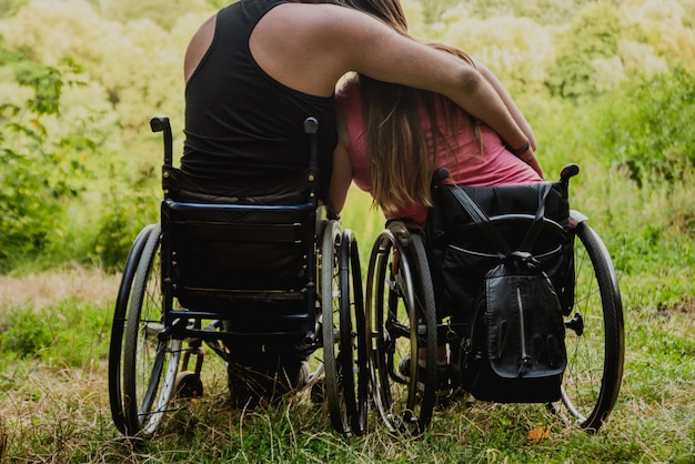 Behindertes paar, das im wald nahe see ruht. rollstühle im wald auf dem natürlichen hintergrund