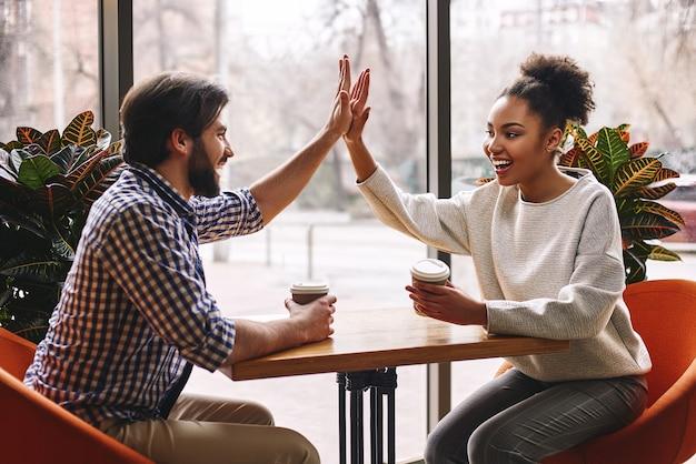 Bei der führung geht es darum, glückliche junge mitarbeiter zusammenzuarbeiten, die high five gratulieren als