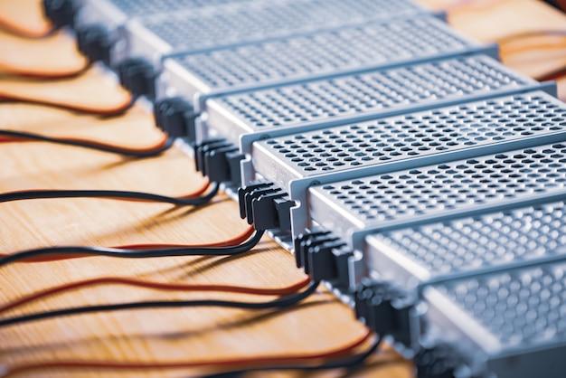 Bei der herstellung von hightech-computern stehen metallgittergehäuse für stromversorgung und kabel auf einem holztisch. konzept der hochtechnologie und industriellen produktion
