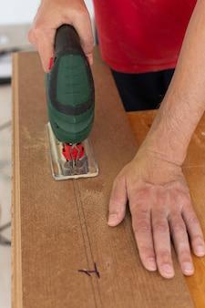 Bei der installation von laminat oder parkett im raum schneidet der arbeiter mit einer stichsäge ein laminat einer bestimmten länge