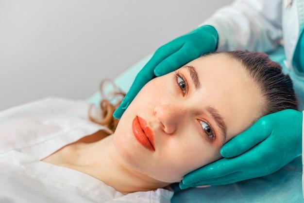 Bei der nasenkorrektur berühren die hände des chirurgen die nase des patienten. menschen, kosmetologie, plastische chirurgie und schönheitskonzept - hände des chirurgen oder der kosmetikerin berühren das weibliche gesicht. speicherplatz kopieren.