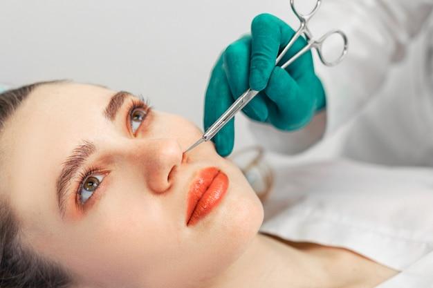 Bei der nasenkorrektur berühren die hände des chirurgen die nase des patienten.