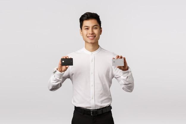 Bei dieser bank wird kein bargeld benötigt. der erfreute und freche hübsche asiatische junge männliche unternehmer, zwei kreditkarten schwarzweiss-platin halten und lächeln zufrieden gestellt, empfehlen zahlungsmethode