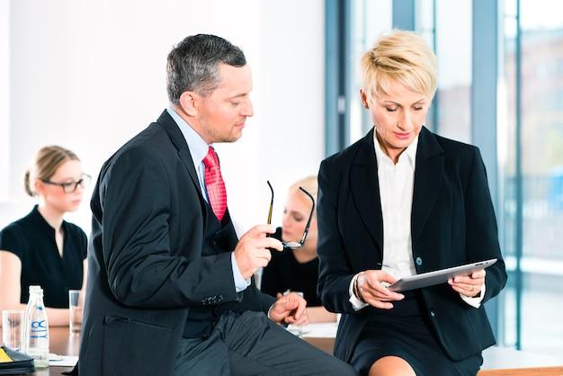 Bei einem geschäftstreffen im büro diskutieren zwei leitende angestellte ein dokument auf einem tablet-computer