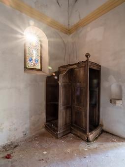 Beichtstuhl einer verlassenen kirche mit der sonne, die durch das bunte fenster hereinkommt