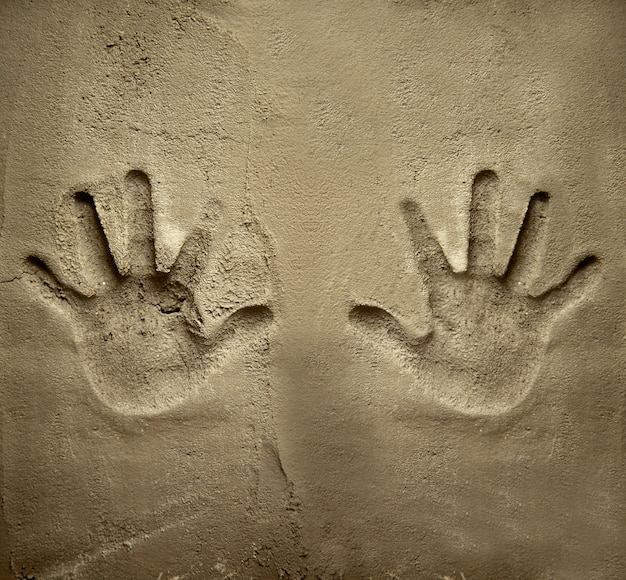 Beide hände bedrucken die zementmörtelwand