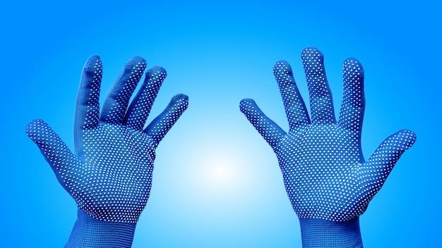 Beide hände in den blauen handschuhen mit dem weißen punktierten muster lokalisiert auf blau