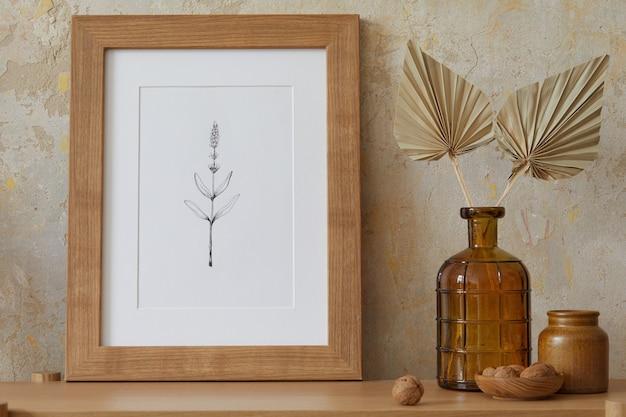 Beige boho-interieur des wohnzimmers mit rahmen, eleganten accessoires, getrockneten blumen in vase, holzkonsole in stilvoller wohnkultur. minimalistisches konzept..