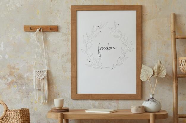 Beige boho-interieur des wohnzimmers mit rahmen, eleganten accessoires, getrockneten blumen in vase, holzkonsole und hängender rattanhütte in stilvoller wohnkultur.