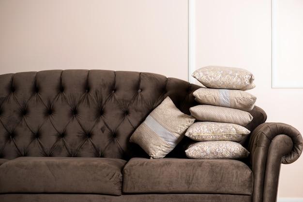 Beige cremekissen mit verzierungen auf schwarzem sofa in der wohnung