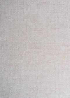 Beige farbe des teppichbeschaffenheitshintergrunds, creme abstraktes baumwolltuch verspotten schablonenstoff auf hintergrund. künstlerische graue wale leinen leinwand textur.