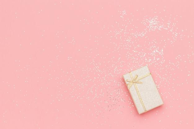 Beige geschenkbox mit bogen in der ecke auf rosa