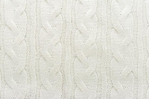 Beige gestrickte stoffwolle textur für hintergrund. nahaufnahme des weißen strickmaterialmusters für design.