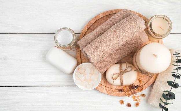 Beige handtücher, seife, kerzen und ein zweig des eukalyptus auf einem weißen hölzernen hintergrund. draufsicht. das konzept der körperpflege.