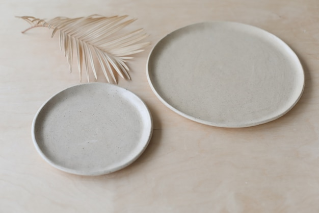 Beige keramikplatte auf einer holztisch-draufsicht. minimalistisches handgemachtes keramikgeschirr und keramik
