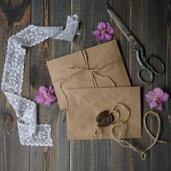 Beige kraftumschläge, alte scheren und rosa violablumen. hochzeits- oder geburtstagseinladung oder mitteilungskonzept und -modell. draufsicht und ebene legen mit kopienraum