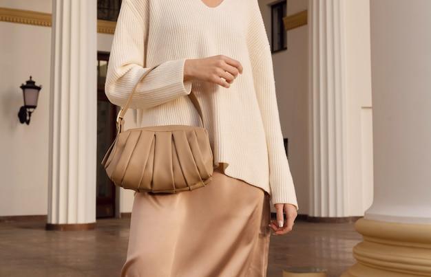 Beige ledertasche der nahaufnahme in der hand der modefrau gekleidet im seidenrock. weibliches elegantes herbst- und frühlingsoutfit.