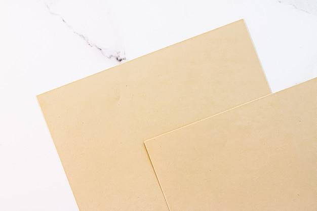 Beige papiere auf weißem marmorhintergrund als büromaterial flach liegend luxus-branding flach und ...