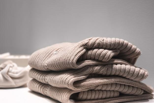 Beige pullover aus natürlichen stoffen werden auf dem tisch gefaltet.