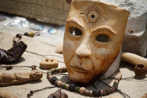 Beige realistische pappmaché-maske mit sonnensymbol auf der stirn, die in den grünen niederlassungen des baums hängt