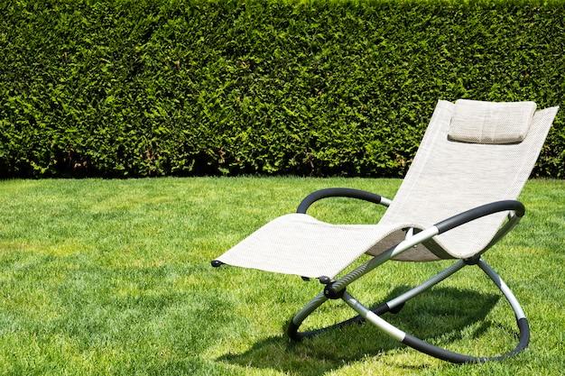 Beige schaukelliege auf grünem gras.