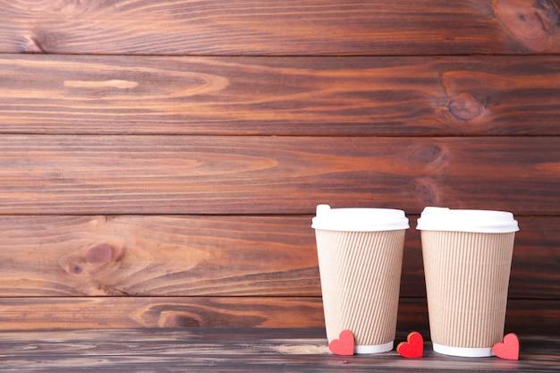 Beige tassen kaffee und herzen auf holzbraun