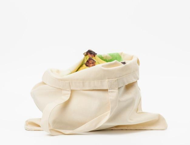 Beige textilbeutel mit frischen früchten auf weißer oberfläche, keine verschwendung