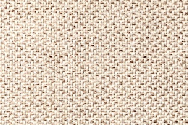 Beige weinlesegewebe mit gesponnener beschaffenheitsnahaufnahme. textilmakrohintergrund