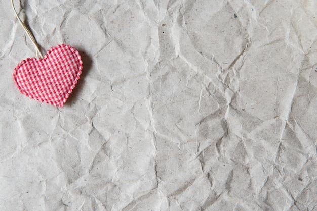 Beige zerknittertes papier mit rosa herzen für valentinsgruß, liebe und hochzeitshintergrund.