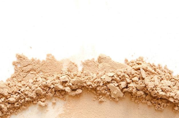 Beige zerschmettertes gesichtspuder für make-up als probe des kosmetischen produktes, lokalisiert
