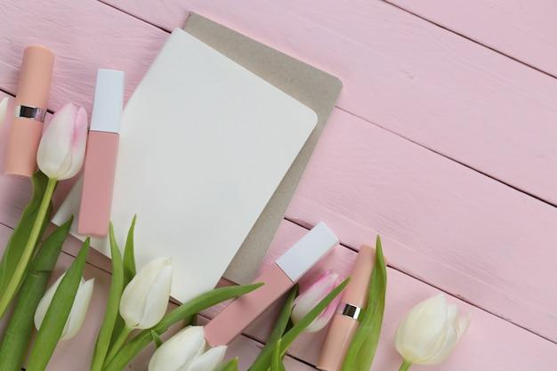 Beiger lippenstift- und lipglosssatz und weiße tulpenblumen