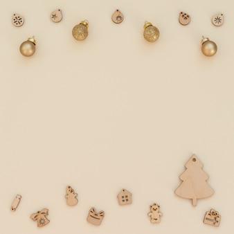 Beiger weihnachtshintergrund mit hölzerner weihnachtsdekoration und goldenen weihnachtskugeln. flacher laienstil mit kopierraum. neujahrsgrußkarte.