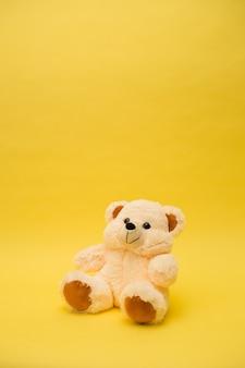 Beiges bärenspielzeug der vertikalen ausrichtung auf einem gelben isolierten hintergrund mit einer kopie des raumes
