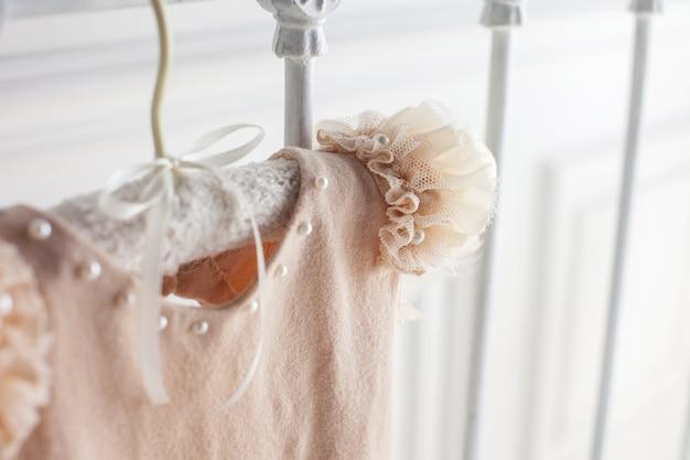 Beiges kleid aus wolle und durchbrochene details. handgemachte sute für baby wiegt auf einem kleiderbügel