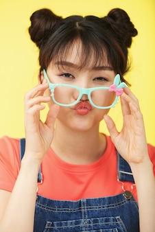 Beiläufig gekleidete junge asiatische frau, die kamera mit hell farbigen gläsern hinunter ihre wekzeugspritze betrachtet
