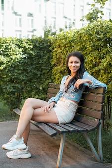 Beiläufige ausstattungsfrau, die auf einer bank sitzt