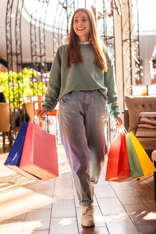 Beiläufige gekleidete frau, die einkaufenbeutel anhält